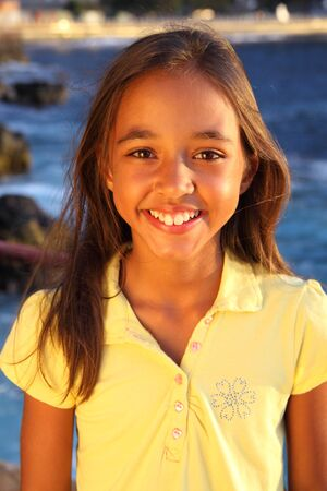 Cute smile from a young girl at the seaside photo
