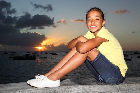 Young school girl with a big smile sitting by the sea at sunset  photo