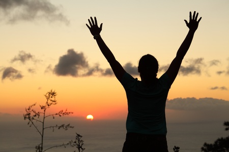 farewell: Woman hiker in silhouette standing arms raised to sunset