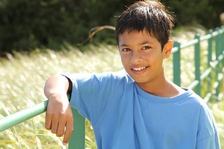 pre teen boys: Boy resting on fence rail in countryside sunshine