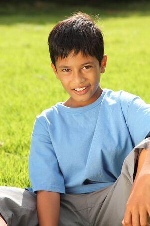 Boy sitting on grass in beautiful bright sunshine photo