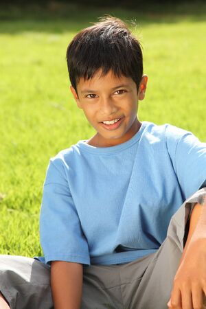 Boy sitting on grass in beautiful bright sunshine photo