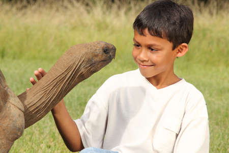 Young boy looks into eyes of a giant tortoise photo