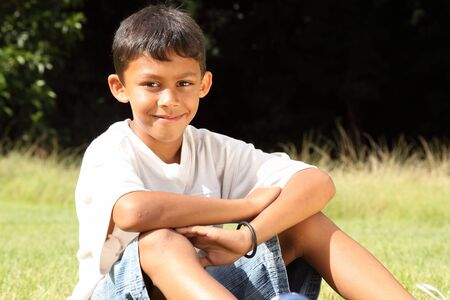 pre adolescent boys: School boy sitting in the park on sunny day
