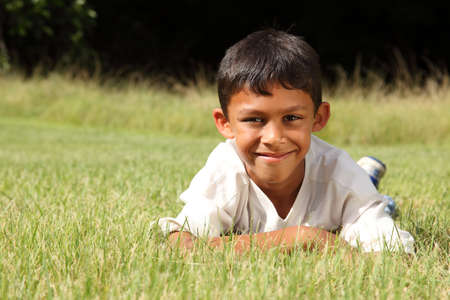 Young ethnic boy lying on the grass in park photo