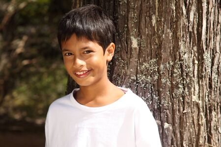 Close up young boy big smile leaning against a tree photo