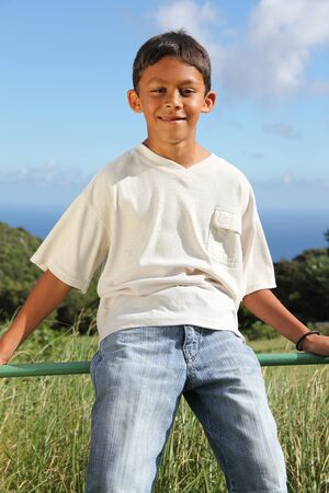pre adolescent boys: Boy sitting on the fence Stock Photo