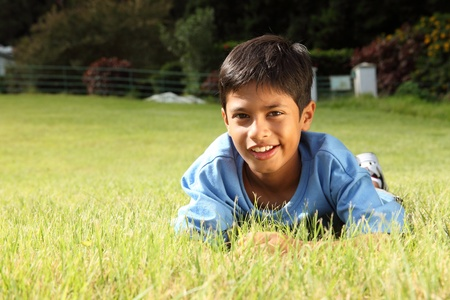Young boy smiling lying on the grass in park photo