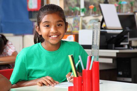 desk tidy: Schoolgirl brilliant smile at her desk in class