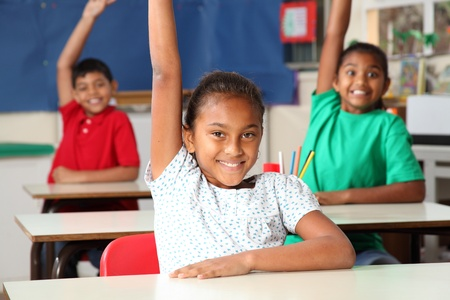 Three young school children arms raised in class Stock Photo - 9746273