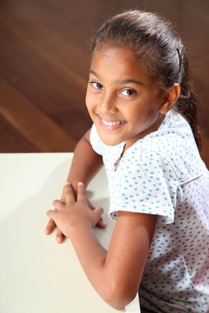 Beautiful smile from young schoolgirl in classroom Stock Photo - 9746280