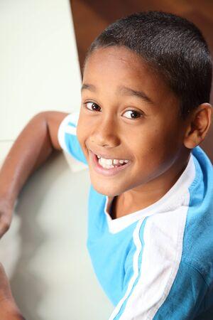 Chico joven escuela �tnicos de retrato 9 sentado en el escritorio de aula Foto de archivo