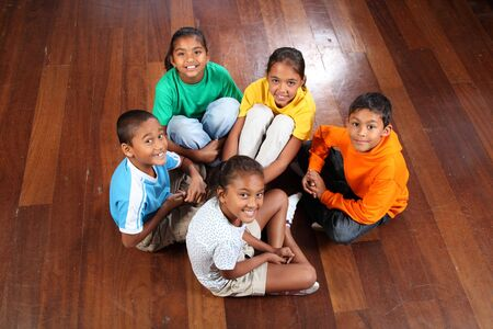 Looking down on group of five happy young primary school children sitting on classroom floor Stock Photo - 9746287