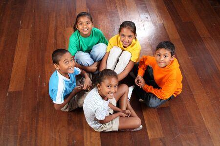 Mirando hacia abajo en el grupo de cinco ni�os de primaria joven feliz sentada en el piso del aula