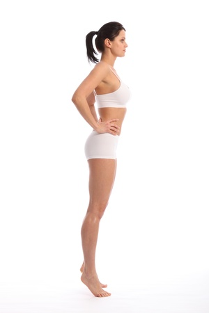 Profile view of beautiful healthy young woman wearing white sports underwear, standing against white background showing off fit body. photo
