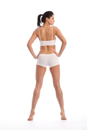 rear view girl: Rear view of beautiful healthy young woman wearing white sports underwear, standing against white background showing off fit body. Stock Photo