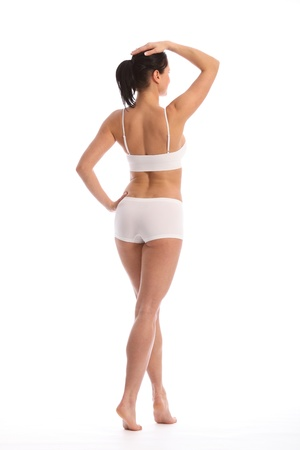 Rear view of beautiful healthy young woman wearing white sports underwear, walking against white background showing off fit body.