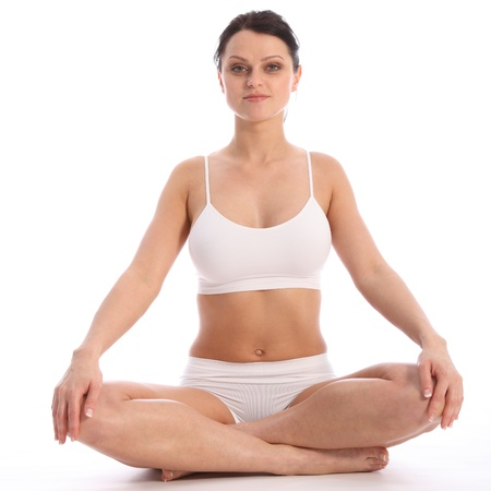 bra top: Beautiful healthy young woman wearing white sports underwear, sitting cross legged on floor against white background showing off fit body. Stock Photo