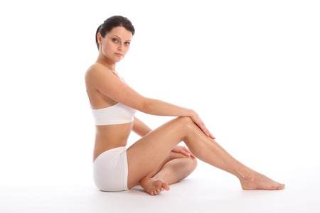 long feet: Beautiful healthy young woman wearing white sports underwear, sitting on floor with one knee raised against white background showing off fit body and long legs. Stock Photo