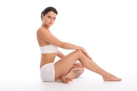 Hermosa mujer saludable de j�venes vestidos de blanco deportes ropa interior, sentados en el piso con una rodilla contra fondo blanco mostrando cuerpo fit y largas piernas.