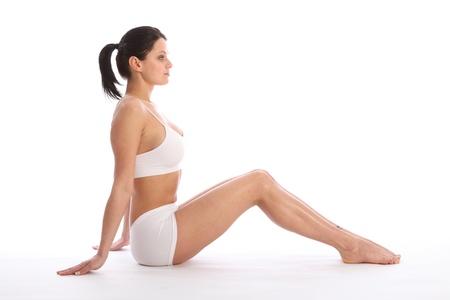 Vista de hermosa mujer joven saludable llevando ropa interior deportiva blanca, sentado en el suelo con las rodillas contra el fondo blanco mostrando cuerpo fit y largas piernas de perfil. Foto de archivo