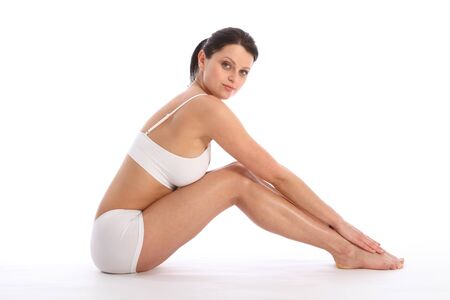 bra top: Profile view of beautiful healthy young woman wearing white sports underwear, sitting on floor with knees raised against white background showing off fit body and long legs.