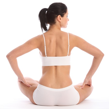 bra top: Beautiful healthy young woman wearing white sports underwear, sitting cross legged on floor against white background showing off fit body. Taken from behind her.