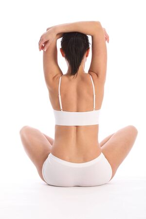 Fit and healthy young woman wearing white sports underwear, sitting cross legged on floor against white background showing off sexy body. Taken from behind her. photo