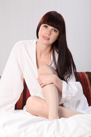 Beautiful happy young woman looks relaxed and casual sitting up in bed wearing white bathrobe. Stock Photo - 9746261