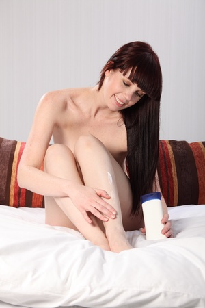 Beautiful happy young woman with a big smile sitting naked in bed, rubbing moisturising cream into her legs. Stock Photo - 9746257
