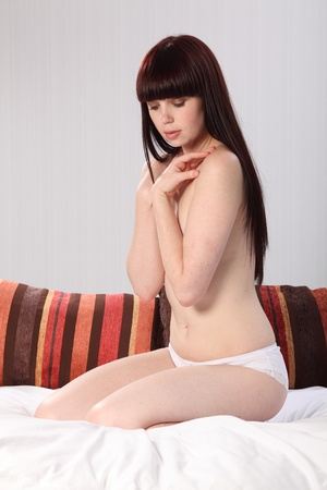 Beautiful half naked young woman with a gentle expression, sitting casually in bed wearing only knickers. photo
