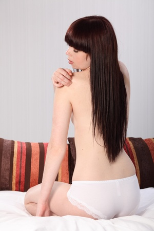 Beautiful half naked young woman sitting in bed, checking for muscle pain in her shoulder. Stock Photo - 9746267