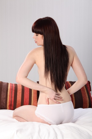 Beautiful half naked young woman sitting in bed, checking for muscle pain in her back. Stock Photo - 9746262