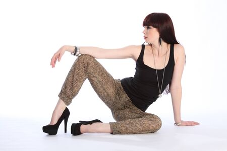 stilleto: Beautiful leggy young red haired fashion model girl strikes a pose in studio, sitting on the floor against white backdrop. Model wearing high heels black vest and leopard print trousers.