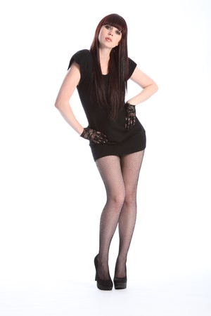 Beautiful sultry young red haired fashion model girl strikes a pose against white backdrop. Model wearing short black dress and high heels showing off long legs. photo