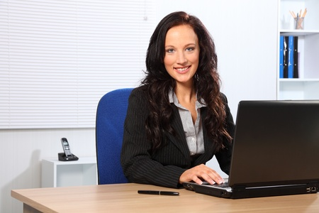 Beautiful young woman working in office looking up from her laptop with a lovely smile photo