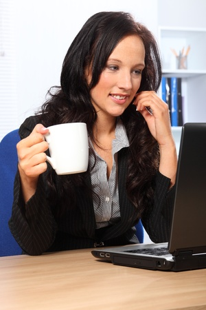 Beautiful young woman enjoying her coffee while working in the office. She has a happy smile and is sitting in front of a laptop wearing a dark business suit. Stock Photo - 9746629