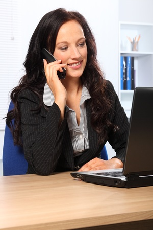 Beautiful young woman speaking on the telephone while working in the office. She has a happy smile and is sitting in front of a laptop wearing a dark business suit. photo