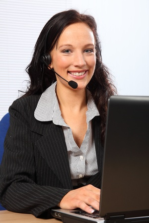 Beautiful young woman providing customer service with a smile, sitting to her computer speaking on a telephone headset. She is wearing a dark business suit. photo