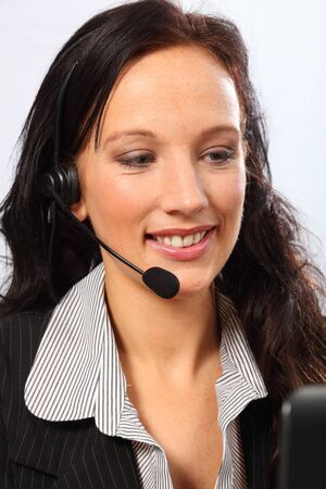Beautiful young woman working in telesales with a smile, sitting to her computer speaking on a telephone headset. She is wearing a dark business suit. photo