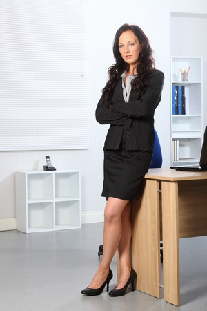 skirt suit: Beautiful young business woman standing in office with her arms folded. She has a serious expression on her face. Stock Photo