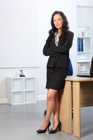 sexy secretary: Mujer de negocios de j�venes hermosas permanente en la Oficina con sus brazos plegados. Tiene una expresi�n seria en su rostro.