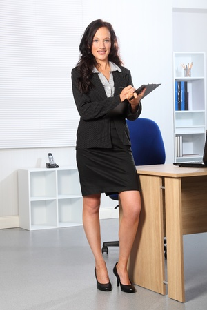 skirt suit: Beautiful young business woman standing in office writing on a clipboard. She has a happy smile on her face.