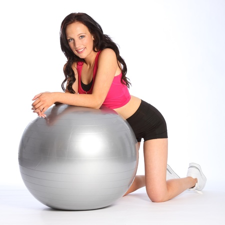 Relaxed and happy, a beautiful young caucasian woman kneels in the gym with silver fitness ball. She is wearing black and pink sports clothes and white trainers.