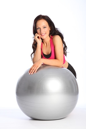 gymnasium: Relaxed and happy, a beautiful young caucasian woman kneels in the gym with silver fitness ball. She is wearing black and pink sports outfit.