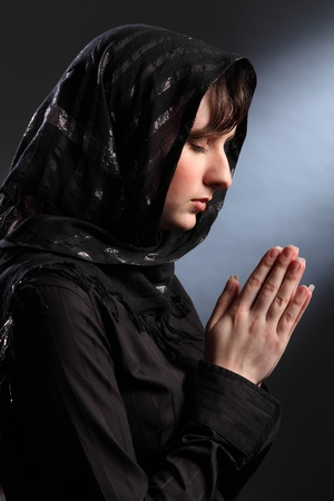 Beautiful young woman wearing black headscarf, eyes closed and hands together in prayer. photo