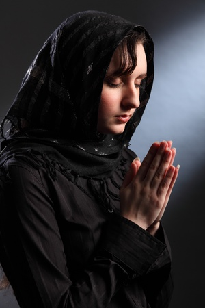 Young religious woman wearing black hijab headscarf, eyes closed and hands together in prayer. photo