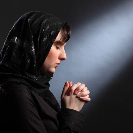 Faith of young religious woman wearing black hijab headscarf, eyes closed and hands together in prayer. photo