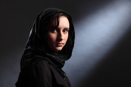 Beautiful young woman wearing black hijab looks quietly at the camera. photo