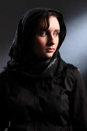 Tranquil portrait of beautiful young woman wearing black hijab, looking away over her shoulder. photo